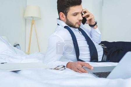 handsome businessman lying on bed while working with laptop and smartphone