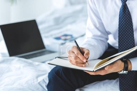 cropped view of businessman writing in diary while sitting on bed with laptop