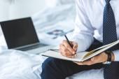 """Постер, картина, фотообои """"обрезанное мнению бизнесмена, записи в дневнике, сидя на кровати с ноутбуком"""""""