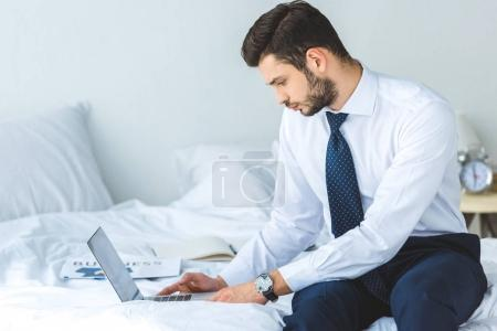 handsome bearded businessman working with laptop in bedroom