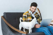 handsome man using laptop and headphones while sitting on sofa with dog