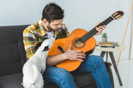 handsome man playing on acoustic guitar and sitting on sofa with dog