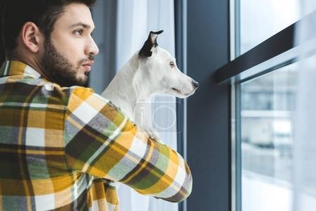 bearded man holding jack russell terrier dog and looking at window