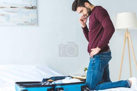 Photo pour Réfléchi jeune homme emballant des bagages sur le lit pour Voyage - image libre de droit