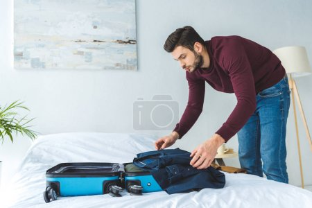 handsome man packing clothes into travel bag for trip