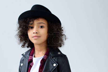 Photo for Close-up portrait of little child in leather jacket and hat looking at camera isolated on grey - Royalty Free Image