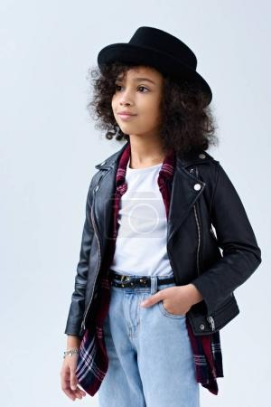 stylish little child in leather jacket looking away isolated on grey