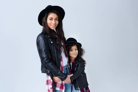 Photo for Stylish beautiful mother and daughter in similar clothes embracing and looking at camera isolated on grey - Royalty Free Image