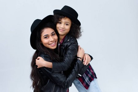 smiling stylish mother and daughter in similar clothes embracing and looking at camera isolated on grey