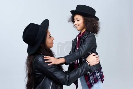 mother and daughter in similar clothes looking at each other isolated on grey