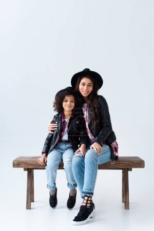 stylish young mother and daughter in similar clothes sitting on bench together isolated on grey