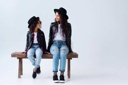 happy mother and daughter in similar clothes sitting on bench together isolated on grey