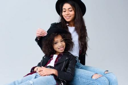 happy mother and daughter in similar clothes spending time together isolated on grey