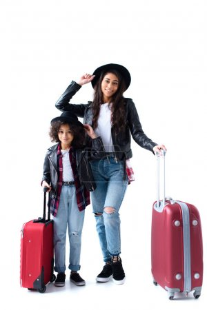 happy young mother and daughter with suitcases isolated on white