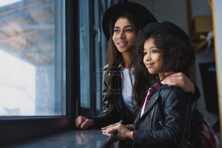 close-up shot of mother and daughter in leather jackets looking at window