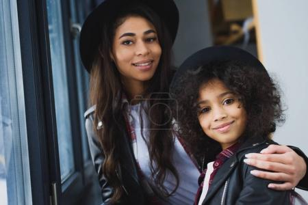 close-up shot of mother and daughter in leather jackets looking at camera