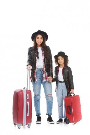 stylish young mother and daughter with luggage isolated on white