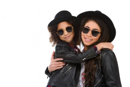 close-up portrait of happy embracing mother and daughter in sunglasses looking at camera isolated on white