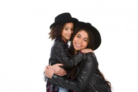 close-up portrait of happy embracing mother and daughter looking at camera isolated on white