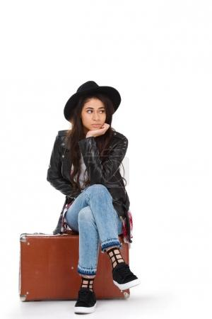 stylish young woman in leather jacket sitting on vintage suitcase isolated on white