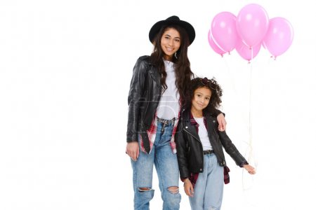 beautiful mother and daughter in similar clothes with pink balloons isolated on white