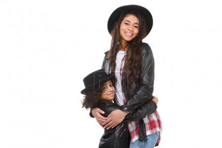 stylish young mother and daughter in leather jackets embracing and looking at camera isolated on white