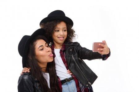 Photo for Stylish mother and daughter taking selfie with smartphone and grimacing isolated on white - Royalty Free Image