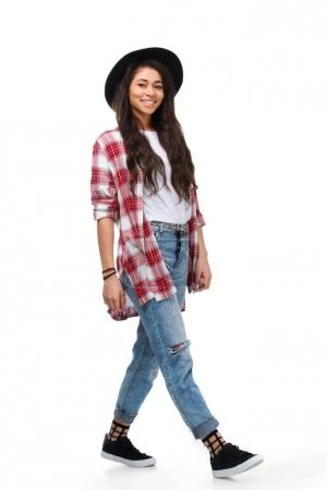beautiful walking young woman in stylish plaid shirt isolated on white