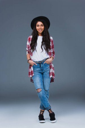 beautiful young woman in stylish clothing and hat on grey