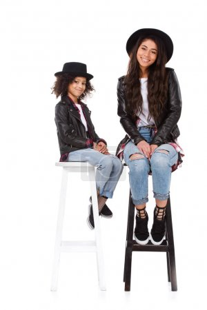 stylish mother and daughter in hats and leather jackets sitting on chairs isolated on white