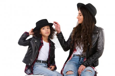 stylish mother and daughter in hats isolated on white