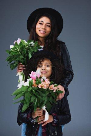 Foto de Madre hermosa e hija en chaquetas de cuero y sombreros con hermosos Ramos de flores aislados en gris - Imagen libre de derechos