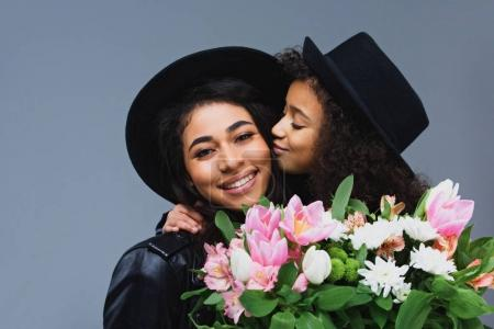 Photo for Daughter kissing her mother while she holding bouquet isolated on grey - Royalty Free Image