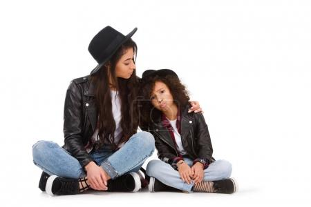 beautiful mother and daughter in leather jackets and hats sitting on floor isolated on white