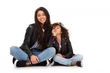 stylish mother and daughter in leather jackets sitting on floor isolated on white