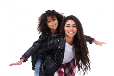 daughter piggybacking on mother and pretending airplane isolated on white