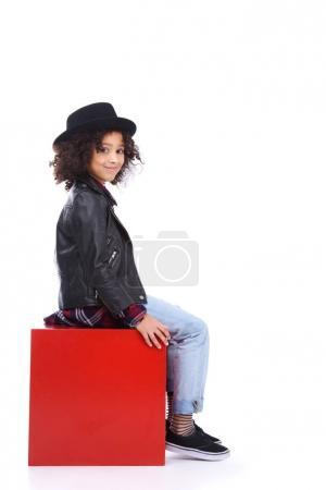 stylish little child sitting on red cube isolated on white