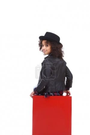 rear view of beautiful little child sitting on red cube isolated on white