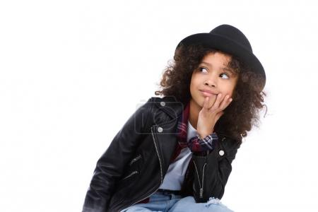 thoughtful little child in stylish leather jacket and hat isolated on white