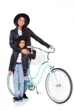 stylish young mother and daughter with bicycle isolated on white