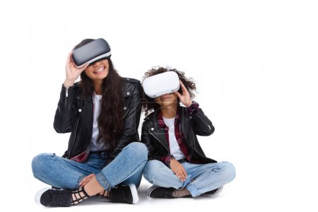 excited young mother and daughter in virtual reality headsets sitting on floor isolated on white