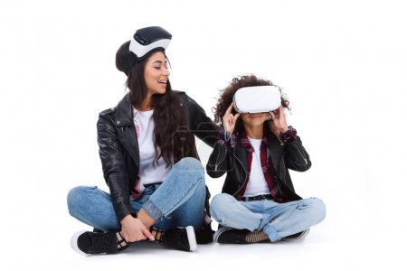 Photo for Happy mother and daughter in virtual reality headsets sitting on floor isolated on white - Royalty Free Image
