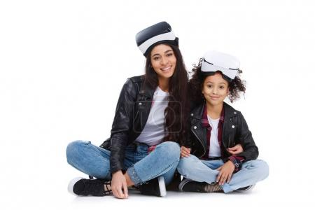 Photo for Young mother and daughter in virtual reality headsets sitting on floor isolated on white - Royalty Free Image