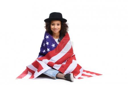 beautiful little child sitting on floor covered in usa flaf isolated on white