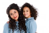 close-up portrait of beautiful mother and daughter looking at camera isolated on white
