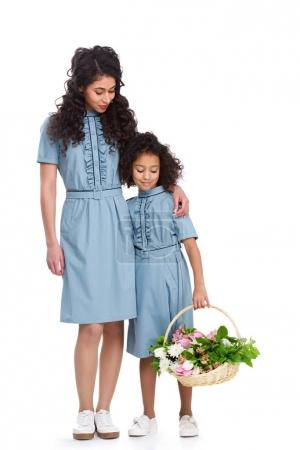 young mother and daughter with basket of flowers isolated on white