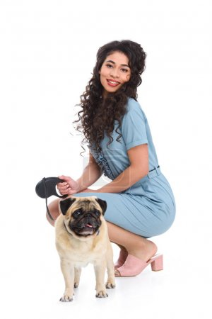 attractive young woman with leashed pug isolated on white