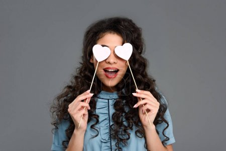 excited young woman covering eyes with hearts on sticks isolated on grey