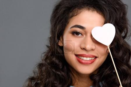 Photo pour Gros plan portrait de souriant yeux couvrant jeune femme avec cœur sur bâton isolé sur fond gris - image libre de droit