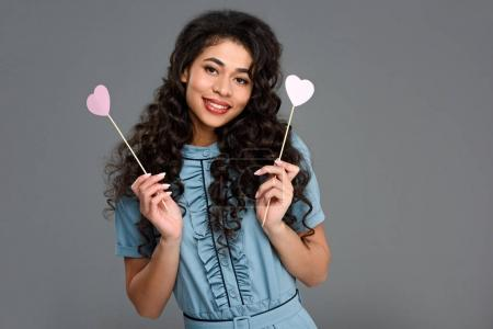 happy young woman with hearts symbols on sticks isolated on grey